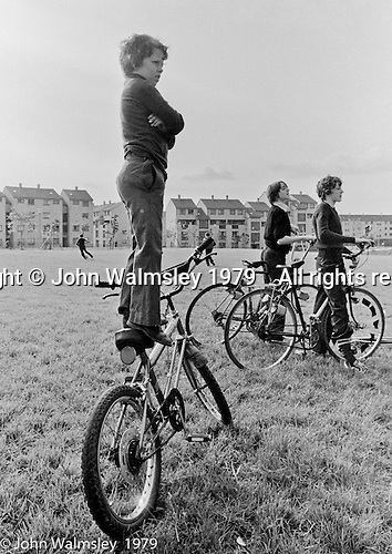 """Balancing on his """"Chopper"""" bike to get a better view, Education Centre, Festival & Gala Day, Wester Hailes, Scotland, 1979.  John Walmsley was Photographer in Residence at the Education Centre for three weeks in 1979.  The Education Centre was, at the time, Scotland's largest purpose built community High School open all day every day for all ages from primary to adults.  The town of Wester Hailes, a few miles to the south west of Edinburgh, was built in the early 1970s mostly of blocks of flats and high rises."""