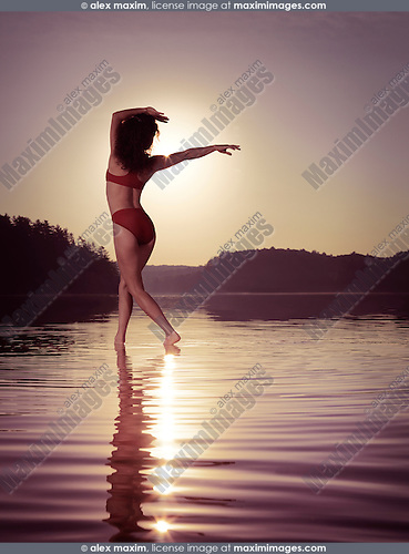 Young woman in swimsuit dancing in the sun on the water in beautiful morning sunrise scenery. Muskoka, Ontario, Canada.