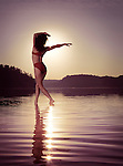 Young woman in swimsuit dancing in the sun on the water in beautiful morning sunrise scenery. Muskoka, Ontario, Canada.