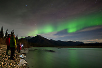 Tourist watch the Aurora borealis reflect in the Koyukuk river, Brooks range,  arctic, Alaska.
