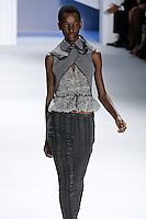 Herieth Paul walks runway in a Grey textured gauze v-neck peplum top with charoal super pique criss cross hooded overlay, and Charcoal striped linen-silk skinny pant, by Vera Wang, for the Vera Wang Spring 2012 collection, during Mercedes-Benz Fashion Week Spring 2012.