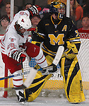 2/12/05  Omaha, NE University of Nebraska at Omaha's Kaleb Betts. runs into Michigan goalie Al Montoya. (photo by Chris Machian/ Prarie Pixel Group)