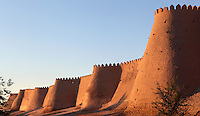 Low angle view of walls of the old city, Khiva, Uzbekistan, pictured on July 6, 2010, at sunrise. Khiva's old city, Ichan Kala, is surrounded by 2.2 kilometres of crenellated and bastioned city walls. Some sections may be 5th century, but the strongest sections were built 1686-88 by Arang Khan. Khiva, ancient and remote, is the most intact Silk Road city. Ichan Kala, its old town, was the first site in Uzbekistan to become a World Heritage Site(1991). Picture by Manuel Cohen.