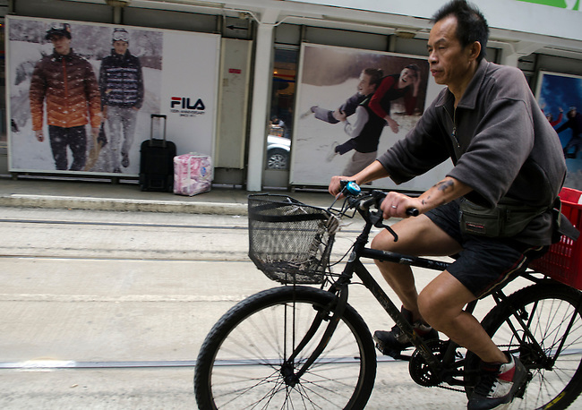 Hong Kong urban scene - delivery man on bicycle pedling through Victoria
