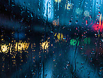 A rain streaked window with blurred city lights