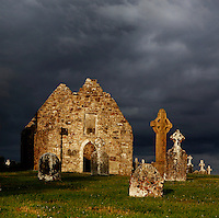 Low angle view of Temple Doolin or Dowling, 10th century, restored 1689, Clonmacnoise, County Offaly,  Ireland, in the evening against a cloudy sky. Clonmacnoise was founded by St Ciaran, with the help of Diarmait Ui Cerbaill, Ireland's first Christian King. The site presents the largest collection of Early Christian graveslabs in Western Europe. Picture by Manuel Cohen