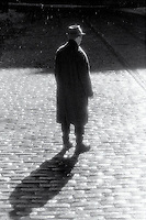 Silhouetted man standing on cobblestone street in the rain