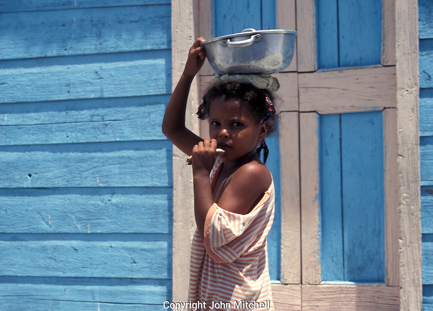 Young girl carrying a cooking pot on her head, Dominican Republic
