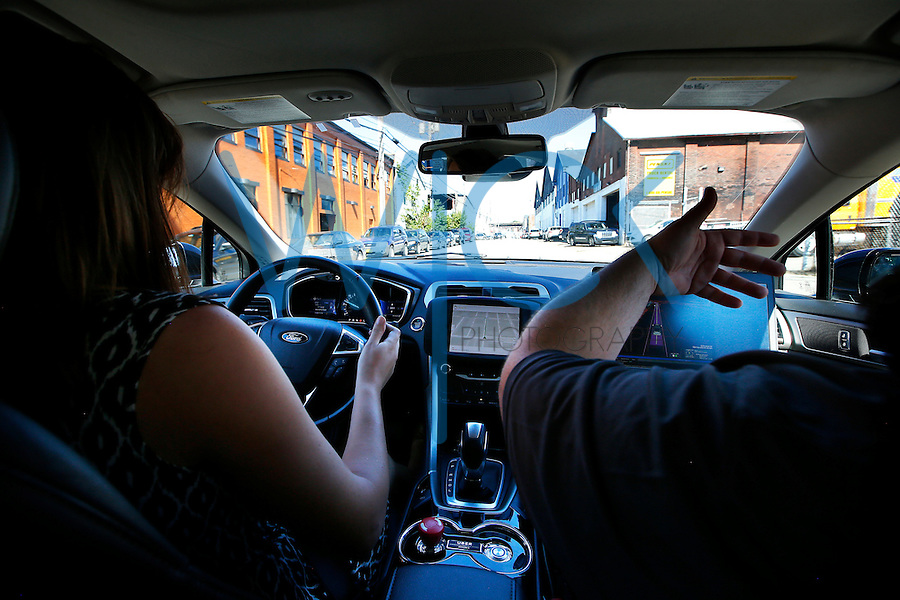 Reporter MJ Slaby sits in the drivers seat of the Uber self-driving Ford Fusion Hybrid car while in autonomous mode during a test drive for members of the media on Tuesday, September 13, 2016 in Pittsburgh, Pennsylvania. (Photo by Jared Wickerham/Wick Photography)