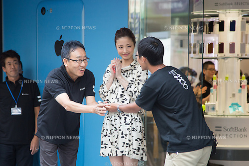 September 20, 2013, Tokyo, Japan - Vice President Ken Miyauchi, left, of Softbank hands an iPhone to the very first buyer at its flagship shop on Tokyo's Ginza main boulevard as sales of Apple's latest smartphones begins across Japan on Friday, September 20, 2013, Actress Aya Ueto, Softbank's commercial charactor, is in center. (Photo by AFLO)