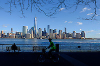 The World Trade Center and New York's lower Manhattan are seen at the background while a man rides his bicycle along a street during a sunny day in the Neighborhood of Exchange Place in New Jersey, 12/15/2015 Photo by VIEWpress