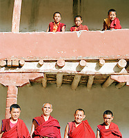 Novice and mature monks on and below monastery balcony, Ladakh, India.