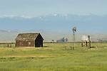 Wooden barn, metal windmill and water tank at the edge of the San Joaquin Valley near the Sierra Nevada Foothills of Merced Co., Calif., in springtime.