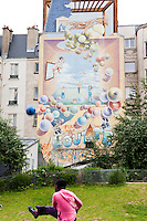A girls playing with a ball. La Goutte d'or is a neighborhood with a large number of african and arab residents. Paris, France.