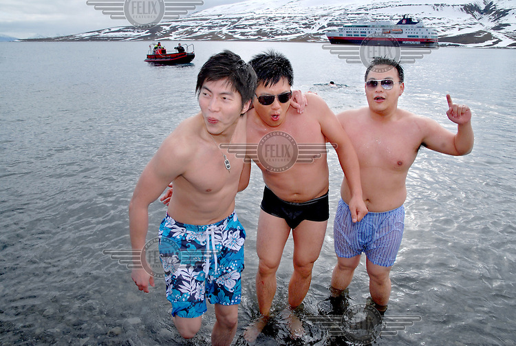 photograph by XAVIER CERVERA 06/2010.Three chinese men after swimming at 1.7 ° C water temperature on the stony beach of Skansbukta, in Billefjorden (close to Longyearbyen capital) in Spitsbergen island, Svalbard archipielago, Norway. Behind them, 'zodiac' for landing, and norwegian vessel MS Fram.