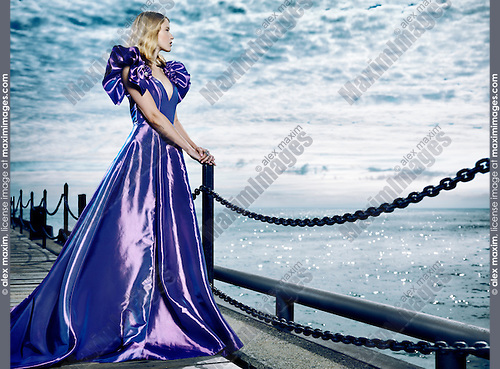 Young blond woman wearing a beautiful long blue dress, evening gown, standing at waterfront looking at the sea