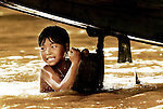 A girl from Muang Ngoi Neua in Laos cools off under a boat in the Ou river.