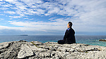 Person meditating sitting on a rock on a shore of a lake. Bruce Peninsula, Ontario, Canada.