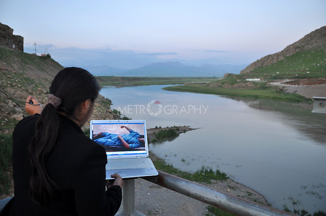 RANYA,IRAQ: A journalist in Ranya views a photograph of a woman who was killed by drowning in the Darband River.  The victim was 17-years-old and her body was discovered eight hours after she was murdered.  No one claimed her body.