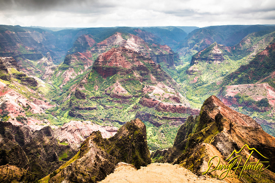 "Waimea  Canyon Splendor. Waimea Canyon, on Kauai's West Side, is described as ""The Grand Canyon of the Pacific."" Although not as big or as old as its Arizona cousin, you won't encounter anything like this geological wonder in Hawaii. Stretching 14 miles long, one mile wide and more than 3,600 feet deep, the Waimea Canyon Lookout provides panoramic views of crested buttes, rugged crags and deep valley gorges. The grand inland vistas go on for miles."