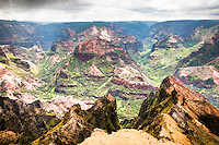 """Waimea  Canyon Splendor. Waimea Canyon, on Kauai's West Side, is described as """"The Grand Canyon of the Pacific."""" Although not as big or as old as its Arizona cousin, you won't encounter anything like this geological wonder in Hawaii. Stretching 14 miles long, one mile wide and more than 3,600 feet deep, the Waimea Canyon Lookout provides panoramic views of crested buttes, rugged crags and deep valley gorges. The grand inland vistas go on for miles."""