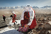Ikhbal (right) arriving at Tash Seri camp, her husband's camp, and kissing on the lip her future mother in law. .With Ikhbal, the recently married woman  moving for the first time to her husband's camp..She just exchanged the red veil of the unmarried girl for the white veil signifying that she is now a married woman...Trekking through the high altitude plateau of the Little Pamir mountains, where the Afghan Kyrgyz community live all year, on the borders of China, Tajikistan and Pakistan.