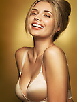 Portrait of a beautiful young happy smiling woman wearing a bra in golden colors isolated on shiny gold background