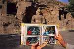 A local photographer touting for business showing his book of Chinese tourists posing for souvenir photos at the Yungang Caves in front of a 14m high Buddha statue...From China [sur]real © Mark Henley..