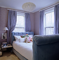 A pale purple colour scheme and velvet upholstered sleigh bed in a teenage girl's bedroom
