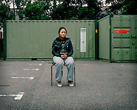 """22 year old Blondine from DR Congo sits outside a drop-in centre for asylum seekers in North London. Blondine's parents were killed in DR Congo because her father was politically active against the government. She was placed in prison at the age of 15 because of her father's activities, where she was raped and tortured, suffering lasting damage to her leg. She managed to escape and arrived alone in the UK in October 2003. In 2004 her asylum claim was refused and she began sleeping on a park bench in Edmonton, """"I started to do sex work in Edmonton. I didn't know how else I could eat."""" In 2008, after years of living destitute, Blondine was granted leave to remain in the UK."""
