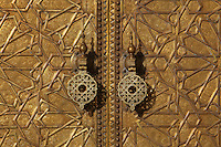 Detail of golden doors and door handles, Royal Palace, 17th century, Fez, Morocco, pictured on February 24, 2009 in the evening. The Royal Palace compound in Fes-el-Jedid covers 80 hectares and contains gardens, mosques and a 14th century Madrasa. As a residence of the king of Morocco it is closed to the public but is impressive even from the outside being especially famed for its golden doors. Fez, Morocco's second largest city, and one of the four imperial cities, was founded in 789 by Idris I on the banks of the River Fez. The oldest university in the world is here and the city is still the Moroccan cultural and spiritual centre. Fez has three sectors: the oldest part, the walled city of Fes-el-Bali, houses Morocco's largest medina and is a UNESCO World Heritage Site;  Fes-el-Jedid was founded in 1244 as a new capital by the Merenid dynasty, and contains the Mellah, or Jewish quarter; Ville Nouvelle was built by the French who took over most of Morocco in 1912 and transferred the capital to Rabat. Picture by Manuel Cohen.