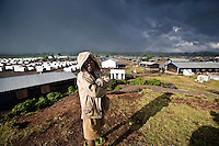 A child stands on the edge of the Kibati camp for displaced people, where thousands have fled to after renewed fighting in the region.