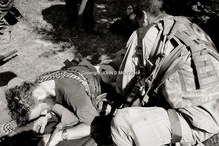 """Photojournalist John D McHugh grimices in pain as a medic examines and dresses his gunshot wound at Kamu Outpost in Nuristan, in north-east Afghanistan, 14 May 2007. The photographer was shot through the stomach during a firefight between the US and Afghan National Army (ANA), who he was embedded with, and insurgents. 17 ANA died, one is still recoreded as """"missing in action"""", and 4 more were wounded. 7 US soldiers were also wounded in the fight. (John D McHugh)"""