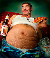 """Spare tire - a man with a huge beer belly that bursts out of his blue jeans holds a """"""""big belly beer"""""""" in one hand and a slice of pizza in the other Billboard and broadcast must be negotiated, due to talent agreement. United States."""