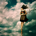 Conceptual image of young Asian woman hovering over water and holding flowers