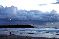 A lone woman looks out to sea on a stormy afternoon with dense cloud hovering over the Cottesloe Beach groyne
