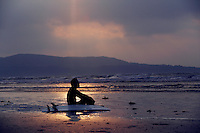 A surfer waits for a wave at sunrise on Dollymount strand Dublin