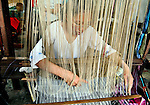 A woman is using traditional Lao silk weaving methods at Carol Cassidy Lao Textiles, Vientiane, Laos.