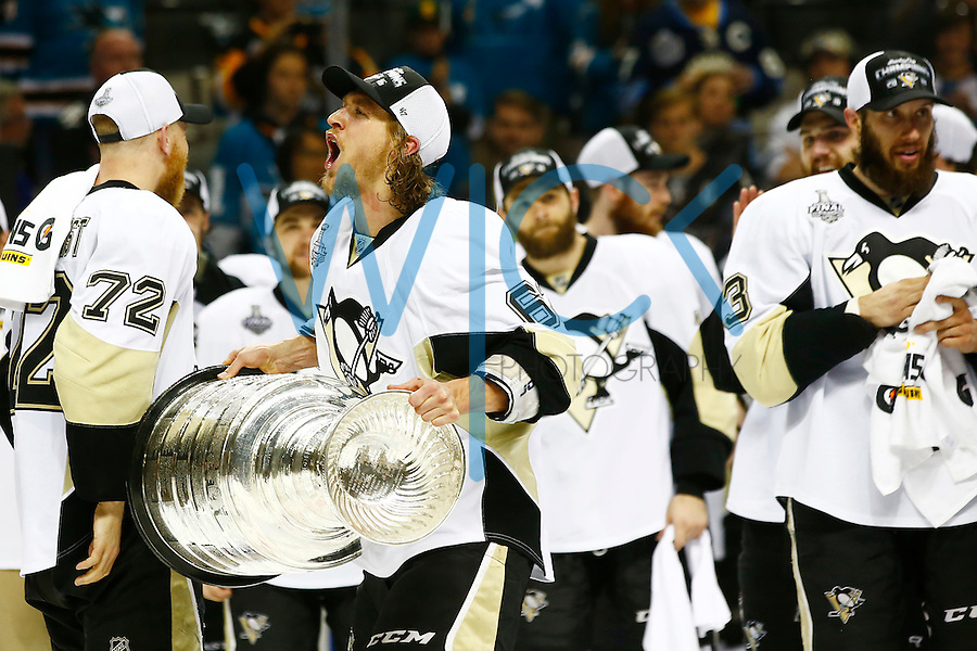 Carl Hagelin #62 of the Pittsburgh Penguins hoists the Stanley Cup following their 3-1 win against the San Jose Sharks during game six of the Stanley Cup Final at SAP Center in San Jose, California on June 12, 2016. (Photo by Jared Wickerham / DKPS)