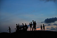 Group of people, including woman with child on her hip, silhouetted against pre-dawn sky. Red Sand Dunes, Mui Ne, Vietnam