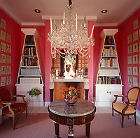 A collection of framed antique prints covers the walls of this pink study which features a large crystal chandelier and tapered bookcases