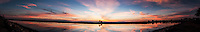 A setting sun paints the sky and is reflected in San Francisco Bay, a sunset panoramic from mulitiple images merged in Photoshop.