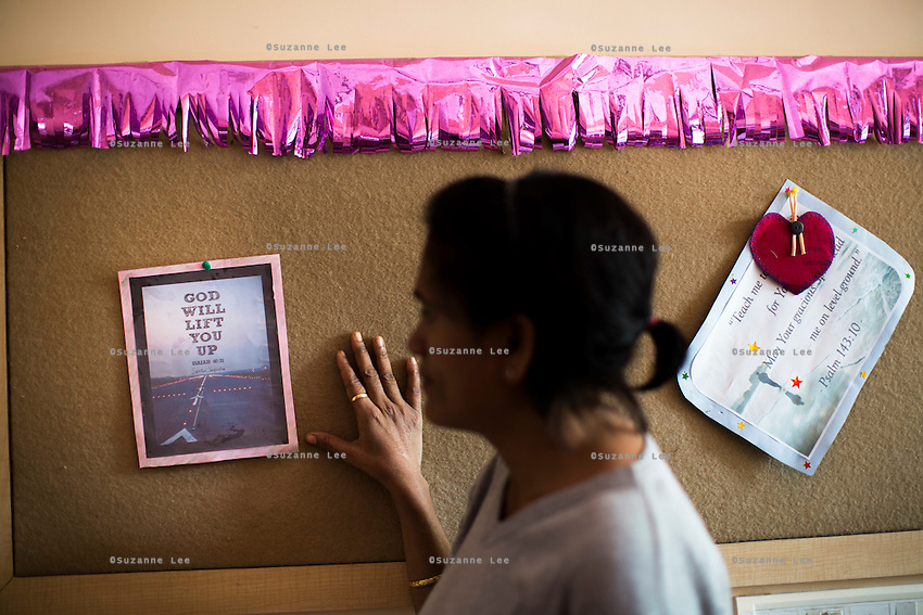 Jasmine (name changed), aged 30, looks at uplifting notes on a corkboard in Nirmal Bhavan, a rehabilitation home for trafficked and rescued girls run by Tearfund partner NGO Oasis India, in Mumbai, Maharashtra, India on 20 February 2014. Jasmine was ten when she was sold for 50,000 Indian Rupees by her family friends who were supposed to look after her. She was beaten, drugged and forced in to prostitution. Rescued from a brothel age 16, she came to live at Nirmal Bhavan and now works for Oasis. Photo by Suzanne Lee/Tearfund