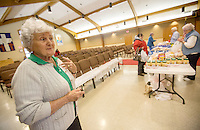 STAFF PHOTO JASON IVESTER --11/13/2014--<br /> Volunteer Ella McGee of Pea Ridge watches as visitors gain supplies at the food pantry on Thursday, Nov. 13, 2014, inside Grace United Methodist Church in Rogers.