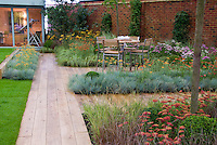 Lawn alternatives with drought tolerant plants: Home and garden with patio furniture table and chairs, outdoor room dining, wooden deck plantings of Achillea, Festuca and other ornamental grasses for xeriscaping dry landscape water-wise plants, brick wall, climbing vines for vertical interest, separate home office, artist's studio in home landscaping