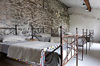 In the childrens' bedroom the four wrought-iron beds were orginally from a convent and the ceramic floor tiles have been brightened with a coat of white paint