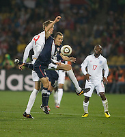 The USA's Steve Cherundolo fights for a header with England's Peter Crouch in the second half of the 2010 World Cup match between USA and England in Rustenberg, South Africa on Saturday, June 12, 2010.