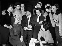 Jimmy O'Dea with girls 'Still at It' Christmas Show at The Gaiety - special for Waveband.17/12/1952..Jimmy O'Dea (26/04/1899 - 07/01/1965) was an Irish actor and comedian..Jimmy O'Dea was born in Lower Bridge Street, Dublin, where his mother kept a small toy-shop. He was one of 11 children. His father was an iron-monger and had a shop in Capel Street. He was educated at Blackrock College and Belvedere College. From a young age he was interested in taking to the stage; he co-founded an amateur acting group, the Kilronan Players, in 1917. But his father would not hear of it. O'Dea was apprenticed to an optician in Edinburgh, Scotland, where he qualified as an optician..He returned to Dublin where, aged 21, he set up his own business which he was, eventually, to give to his sister, Rita. In his spare time he took part in amateur productions of Ibsen and Chekhov. From 1920 he was in the Irish theatre in Hardwicke Street working with actor-producer John McDonagh. After working in plays by Shaw for a few years he rejoined McDonagh in revues, the first of which, Dublin To-Night, was produced at the Queen's Theatre in 1924. In 1927 he took to the stage full-time. In 1928, this company's first production Here We Are won international acclaim, and in December of the same year it produced its first Christmas Pantomime, Sinbad the Sailor..O'Dea made some film appearances, such as Darby O'Gill and the Little People (1959) in which he played King Brian of the little people and Johnny Nobody (1961). He also had a successful career in pantomime and toured Ireland and England many times, and is much associated with actress Maureen Potter (1925-2004), with whom he often partnered..O'Dea was also a prolific songwriter in his day. Many of his songs are still well known to this day..O'Dea married Ursula Doyle. Maureen Potter was bridesmaid. Seán Lemass was best-man; he would also give the valedictory oration at O'Dea's funeral in 1965..