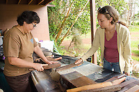 A woman learns how to make kapa or tapa with Roen Hufford, Big Island.