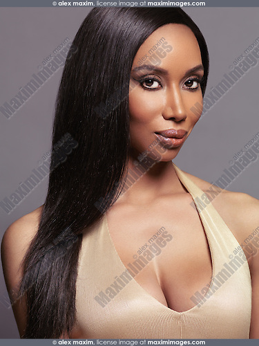 Beauty portrait of young african american woman with long straight hair on gray background